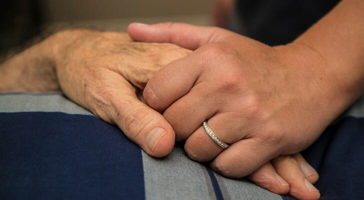 Dying person holds hands with a loved one